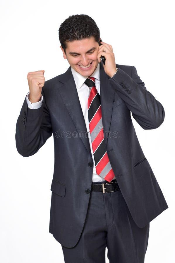 Hombre de negocios en el teléfono que sonríe sobre buenas noticias fotografía de archivo libre de regalías