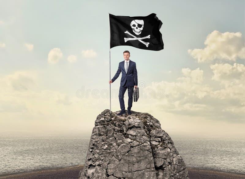Hombre de negocios en el top de una roca que sostiene la bandera de pirata fotografía de archivo