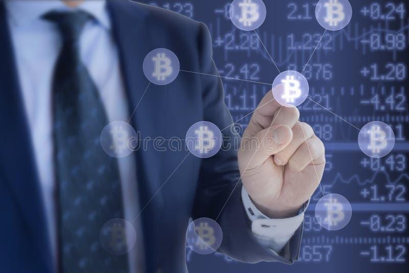 Hombre de negocios en el traje azul que presiona un icono del bitcoin imagen de archivo