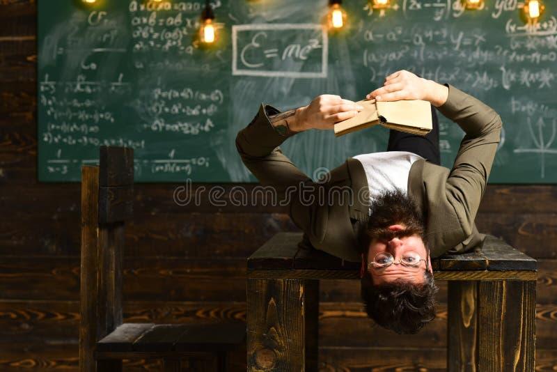 Hombre de negocios en el traje leído en el escritorio de la escuela El hombre barbudo leyó el libro en sala de clase Inconformist fotos de archivo