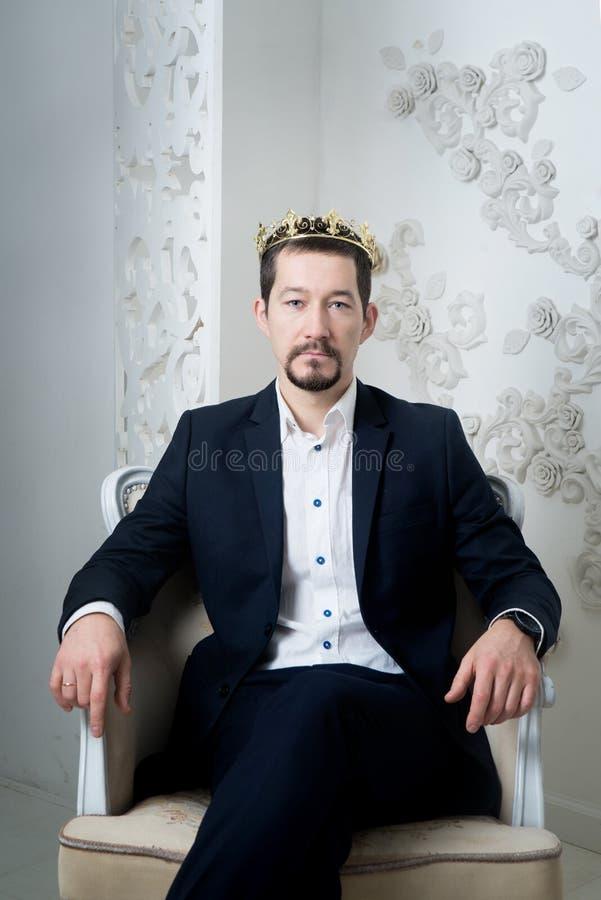 Hombre de negocios en el traje moderno, traje que se sienta en silla con la corona de oro foto de archivo libre de regalías