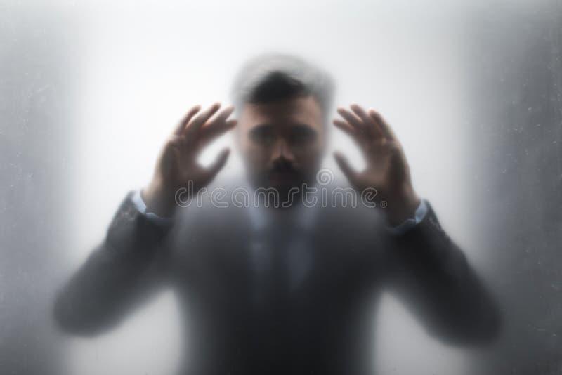 Hombre de negocios en el traje negro que mira a través del vidrio fotografía de archivo