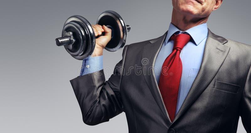 Hombre de negocios en el traje que aumenta pesa de gimnasia Concepto de la presión fiscal fotos de archivo libres de regalías