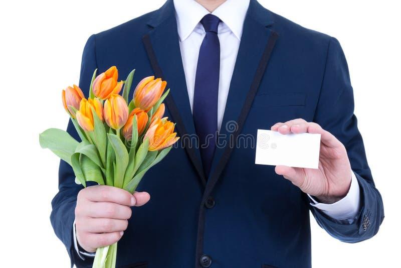Hombre de negocios en el traje que lleva a cabo las flores y la ISO en blanco de la tarjeta de visita imagenes de archivo