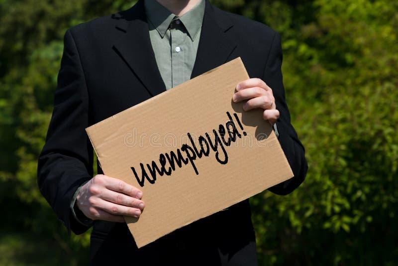 Hombre de negocios en el traje que lleva a cabo una muestra de la cartulina foto de archivo libre de regalías