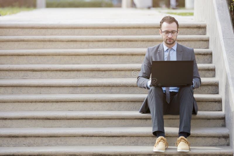 Hombre de negocios en el traje que se sienta en las escaleras y que trabaja en el ordenador portátil foto de archivo