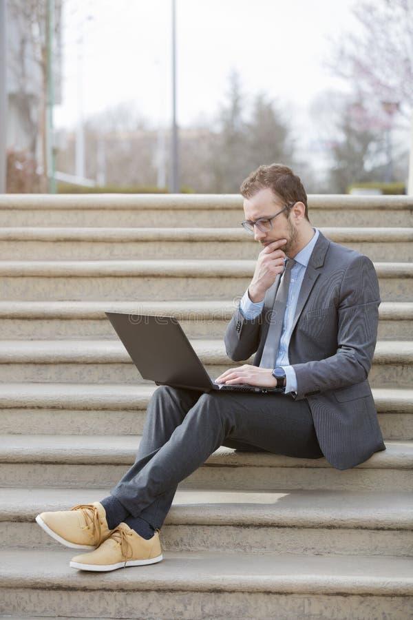 Hombre de negocios en el traje que se sienta en las escaleras y que usa el ordenador portátil imagen de archivo