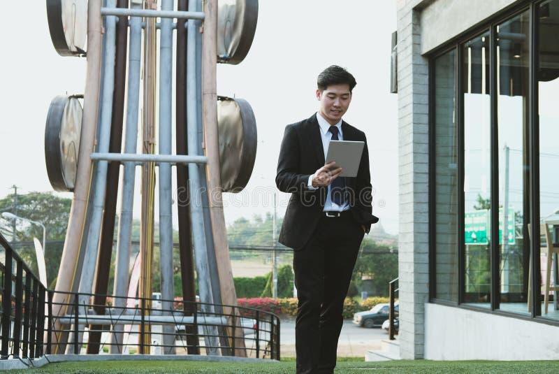 Hombre de negocios en el traje que sostiene el panel táctil mientras que camina fuera de estructura imagen de archivo libre de regalías
