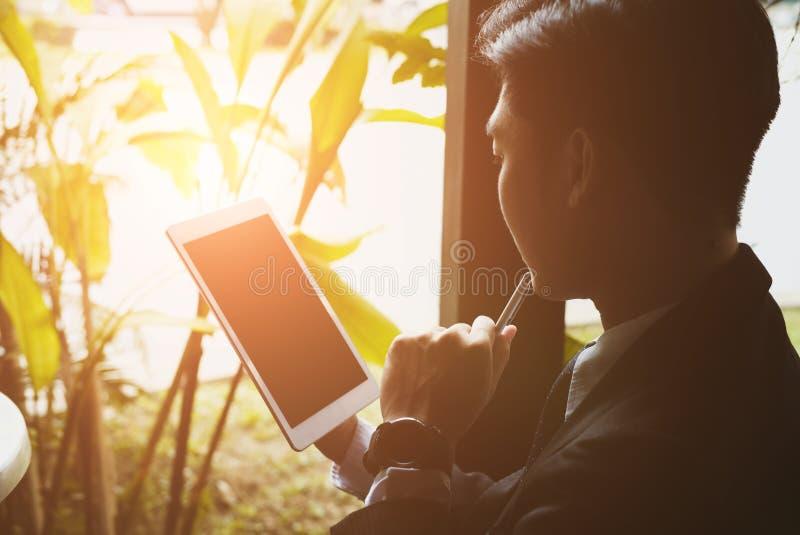 Hombre de negocios en el traje que sostiene el panel táctil mientras que se sienta en el café Youn imagen de archivo