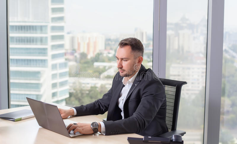 Hombre de negocios en el traje que trabaja en el ordenador portátil fotografía de archivo