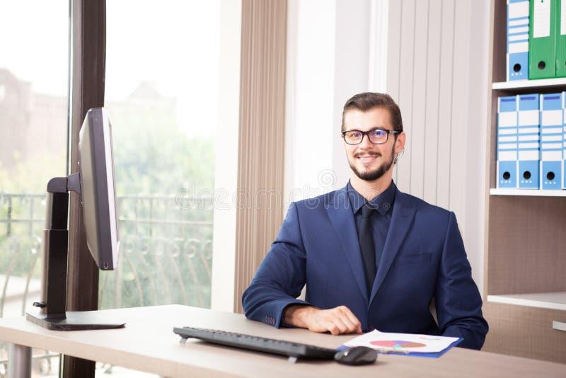 Hombre de negocios en el traje que trabaja en su ordenador al lado de un viento de cristal fotos de archivo