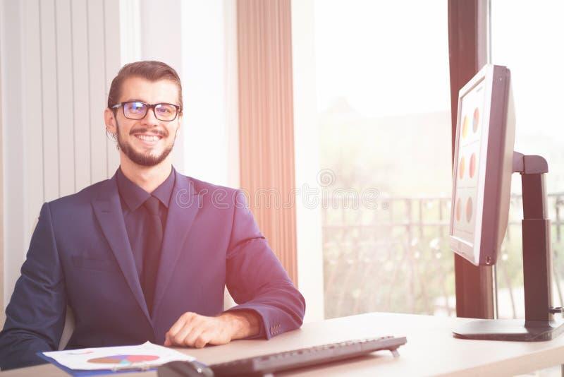 Hombre de negocios en el traje que trabaja en su ordenador al lado de un viento de cristal imagen de archivo
