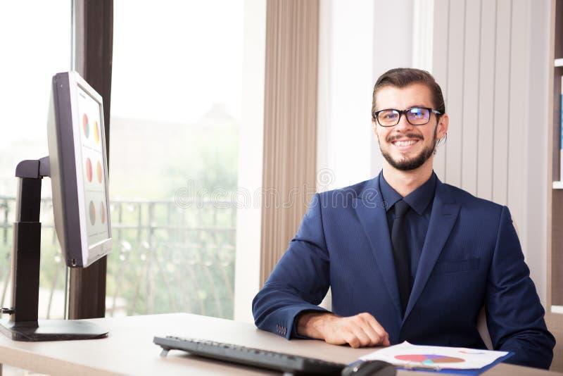 Hombre de negocios en el traje que trabaja en su ordenador al lado de un viento de cristal foto de archivo libre de regalías