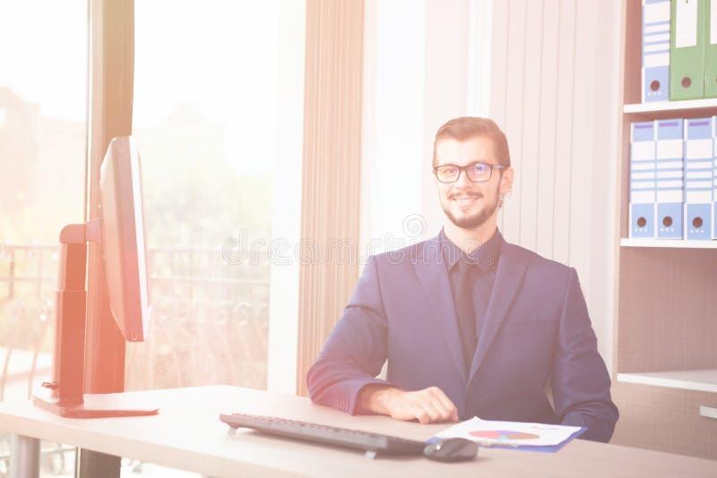 Hombre de negocios en el traje que trabaja en su ordenador al lado de un viento de cristal imagen de archivo libre de regalías