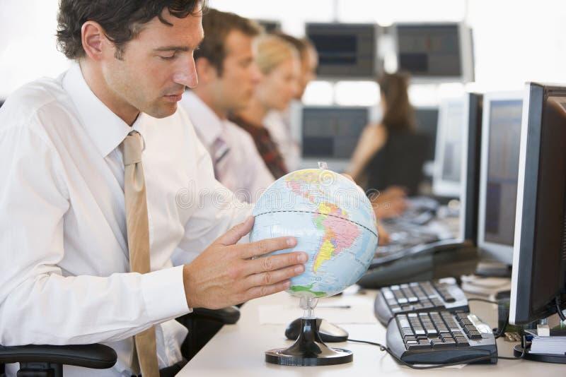 Hombre de negocios en espacio de oficina con un globo del escritorio fotos de archivo libres de regalías