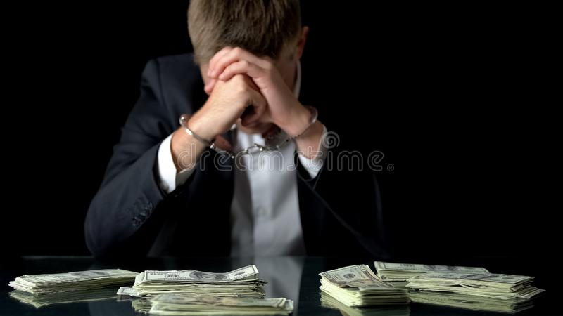 Hombre de negocios en esposas, dinero del trastorno que miente en la tabla, fraudes de la corrupción, soborno foto de archivo