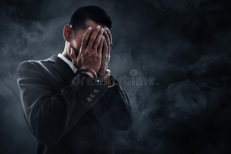 Hombre de negocios en esposas en fondo del humo foto de archivo libre de regalías