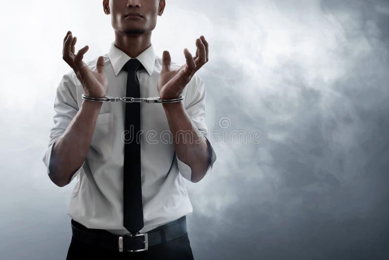 Hombre de negocios en esposas en fondo del humo imagen de archivo