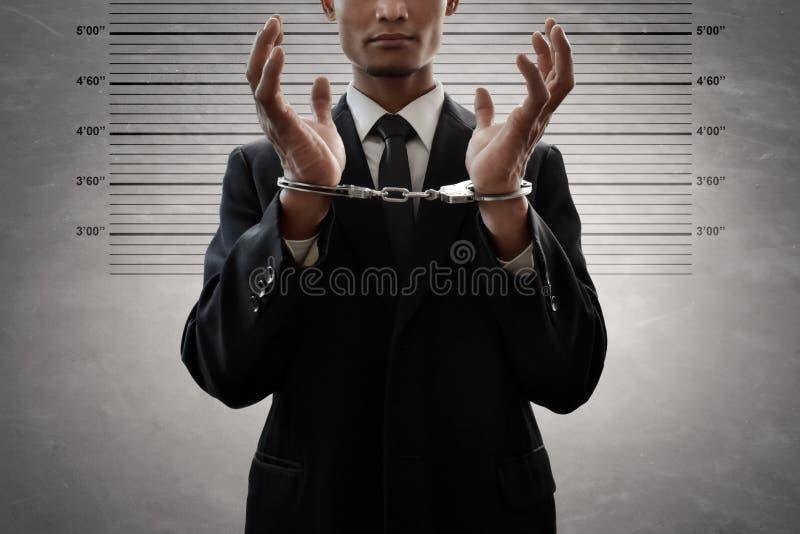 Hombre de negocios en esposas en fondo del mugshot fotografía de archivo libre de regalías
