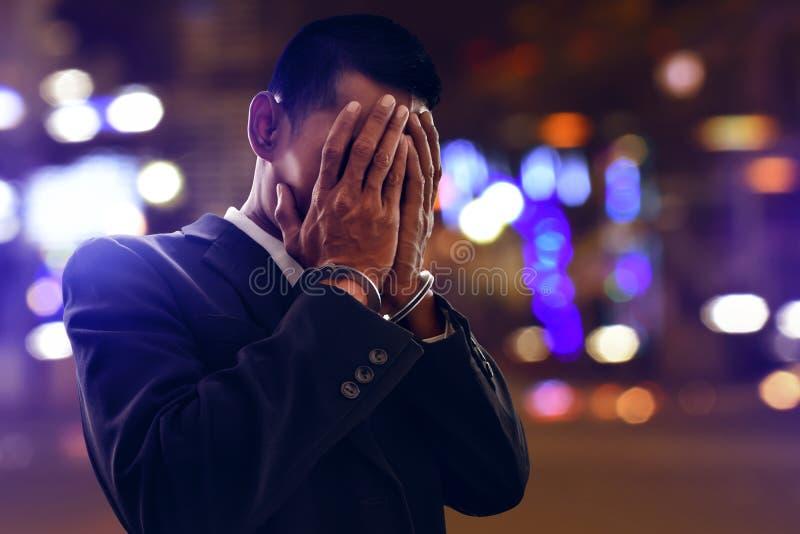 Hombre de negocios en esposas en la noche fotografía de archivo libre de regalías