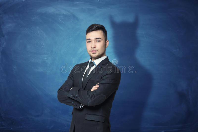 Hombre de negocios en fondo azul de la pizarra con su sombra que tiene cuernos del diablo imagen de archivo libre de regalías