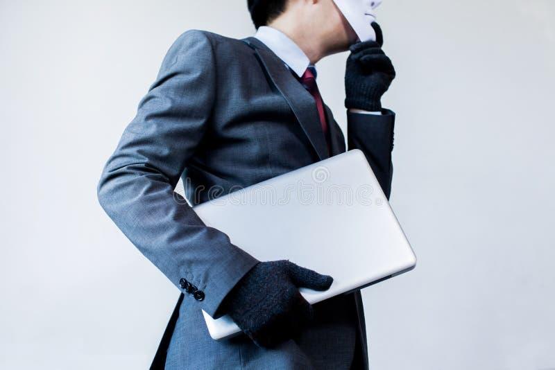 Hombre de negocios en guantes de la máscara blanca y ordenador del robo que llevan e información digital - fraude, pirata informá fotos de archivo