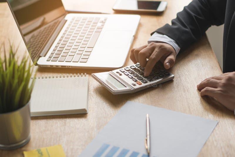 Hombre de negocios en la calculadora y presupuesto del repaso en plan empresarial fotografía de archivo