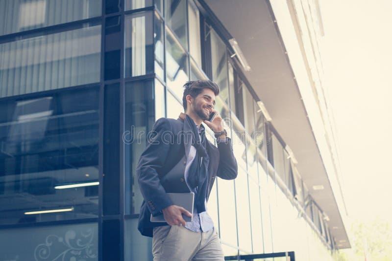 Hombre de negocios en la calle que sostiene iPod y que habla en móvil fotografía de archivo
