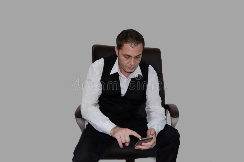 Hombre de negocios en la camisa blanca y el chaleco negro que localizan en la silla y que comprueban su teléfono aislado fotos de archivo libres de regalías