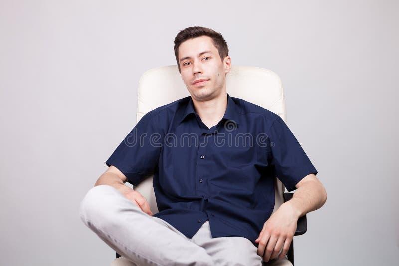Hombre de negocios en la camisa sport que se sienta en una silla de la oficina imágenes de archivo libres de regalías