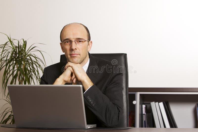 Hombre de negocios en la computadora portátil en oficina fotos de archivo