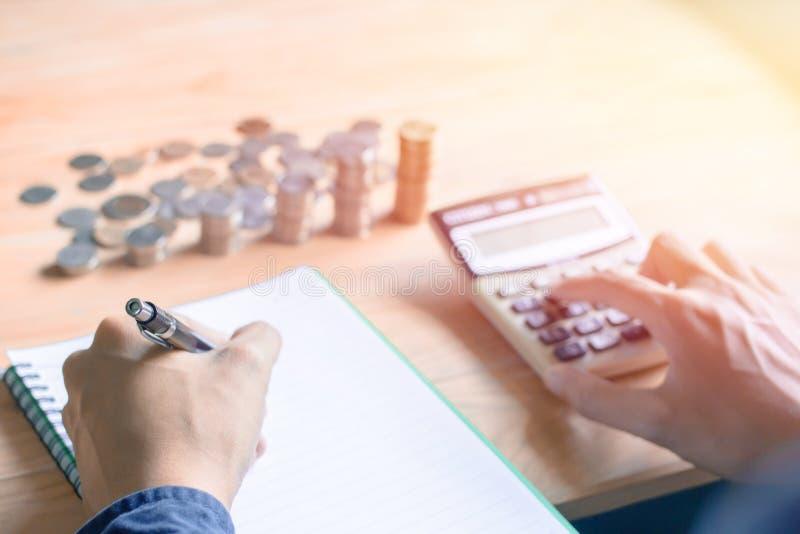 Hombre de negocios en la escritura azul de la pluma de tenencia de la mano de la camisa, el cálculo con la calculadora y datos fi imagen de archivo libre de regalías