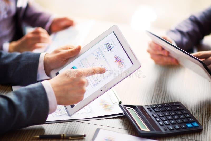 Hombre de negocios en la evaluación financiera en línea sobre una tableta Trabajo del equipo en oficina imagen de archivo