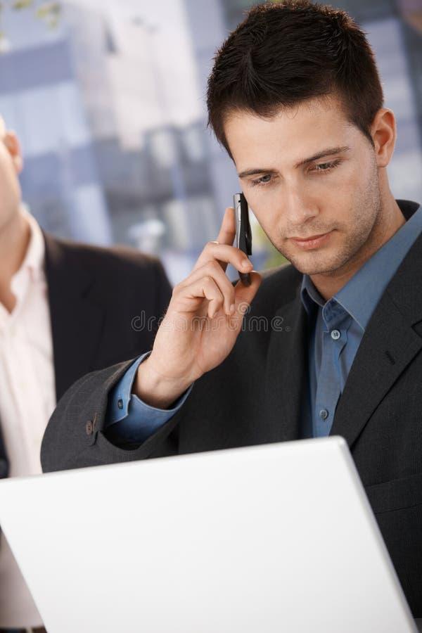 Hombre de negocios en la llamada que sostiene la computadora portátil imágenes de archivo libres de regalías