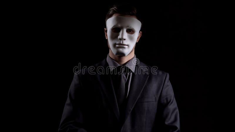 Hombre de negocios en la máscara anónima que mira la cámara, esquemas de la corrupción, fraude imagenes de archivo