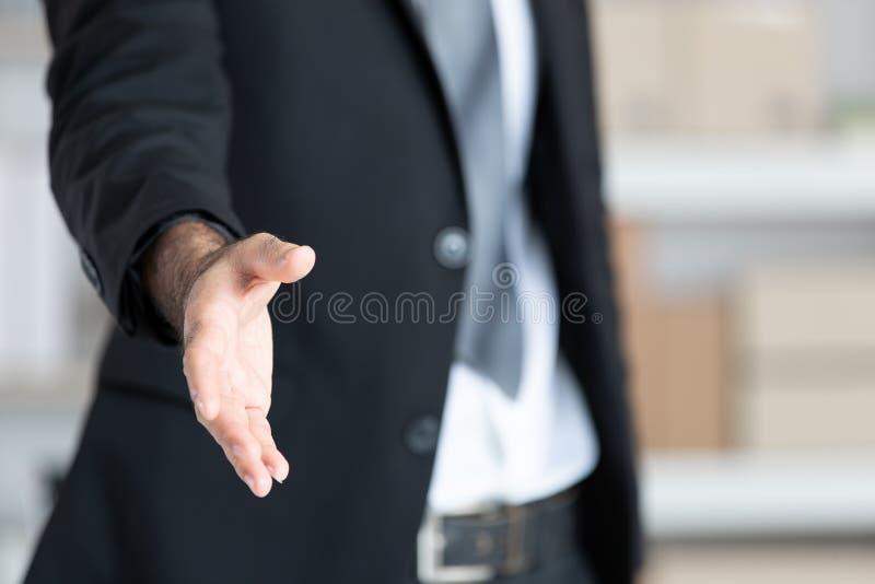 Hombre de negocios en la mano abierta del traje negro lista para sacudir las manos, par foto de archivo