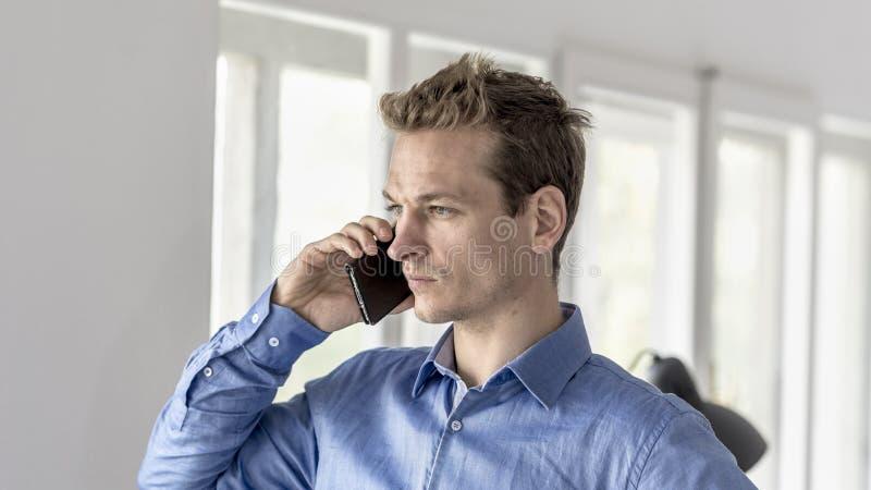 Hombre de negocios en la oficina que tiene una conversación sobre un teléfono móvil imagen de archivo libre de regalías