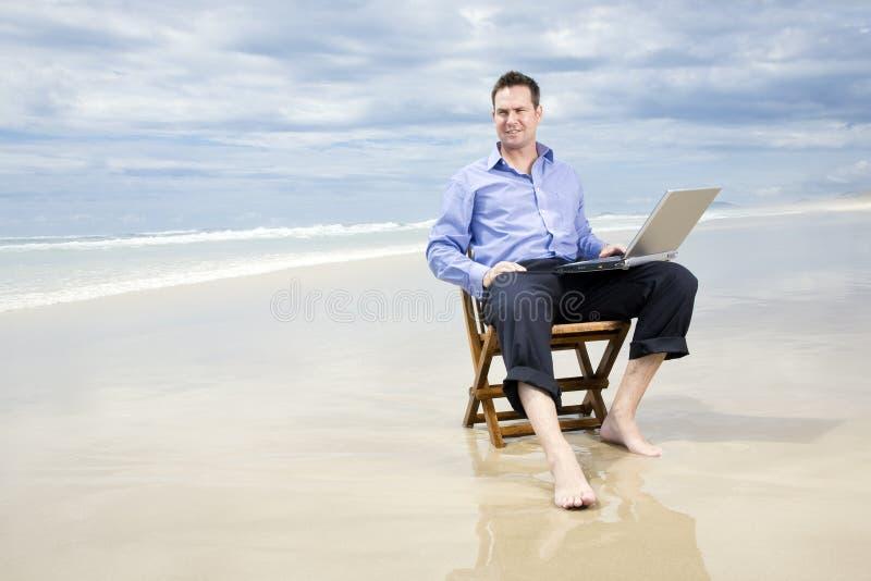 Hombre de negocios en la playa con la computadora portátil imagenes de archivo
