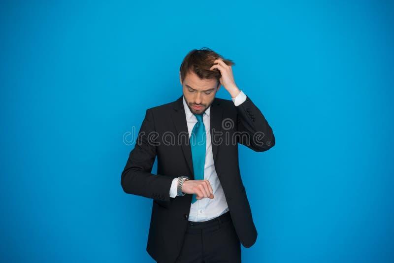 Hombre de negocios en la precipitación que mira su reloj, corriendo tarde foto de archivo libre de regalías