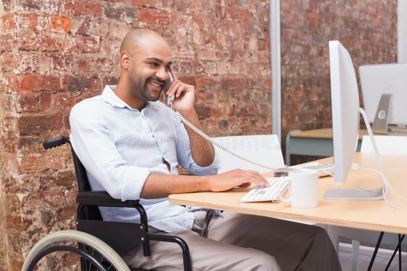 Hombre de negocios en la silla de ruedas que trabaja en su escritorio en el teléfono fotos de archivo libres de regalías