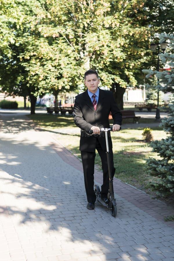 Hombre de negocios en la vespa en el parque foto de archivo