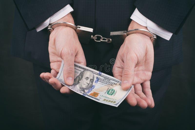 Hombre de negocios en las esposas que sostienen el soborno cientos dólares foto de archivo