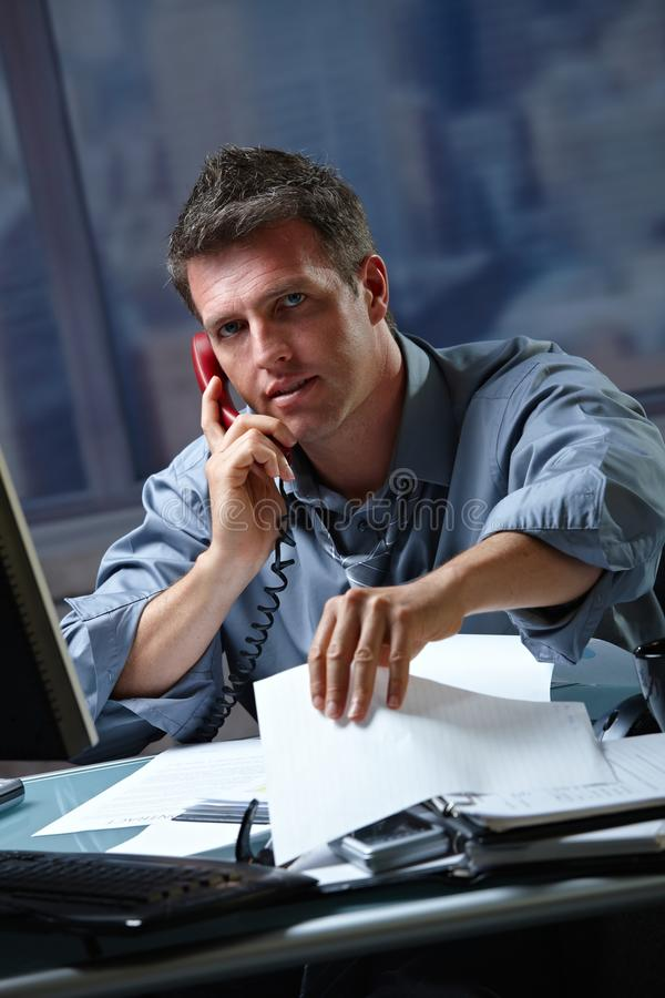 Hombre de negocios en llamada en en horas extras fotos de archivo libres de regalías