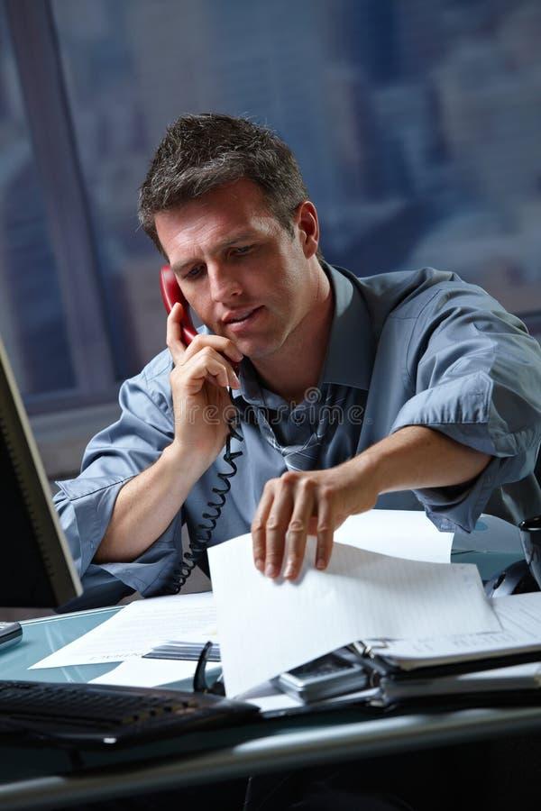 Hombre de negocios en llamada en en horas extras fotografía de archivo libre de regalías