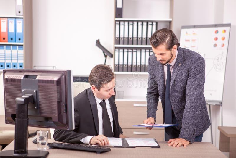 Hombre de negocios en los trajes formales que trabajan en oficina foto de archivo