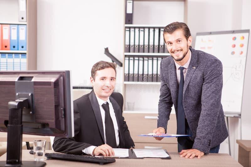 Hombre de negocios en los trajes que trabajan en oficina fotos de archivo libres de regalías