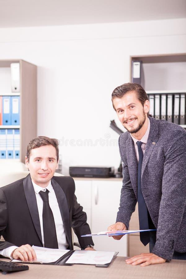 Hombre de negocios en los trajes que trabajan en oficina fotos de archivo