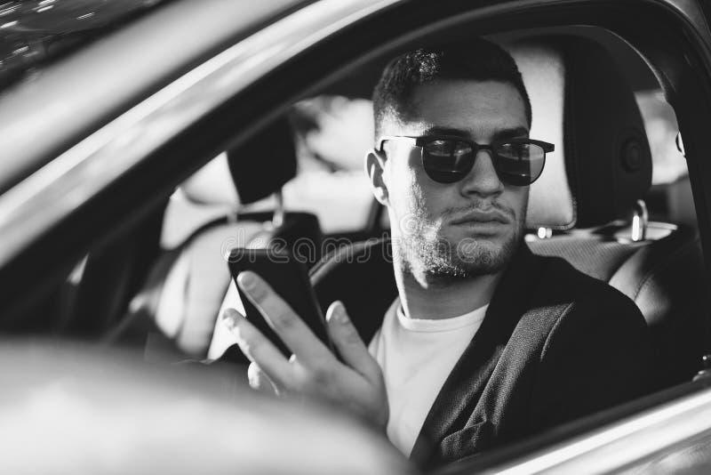 Hombre de negocios en mensaje de la lectura del coche en smartphone imagen de archivo libre de regalías