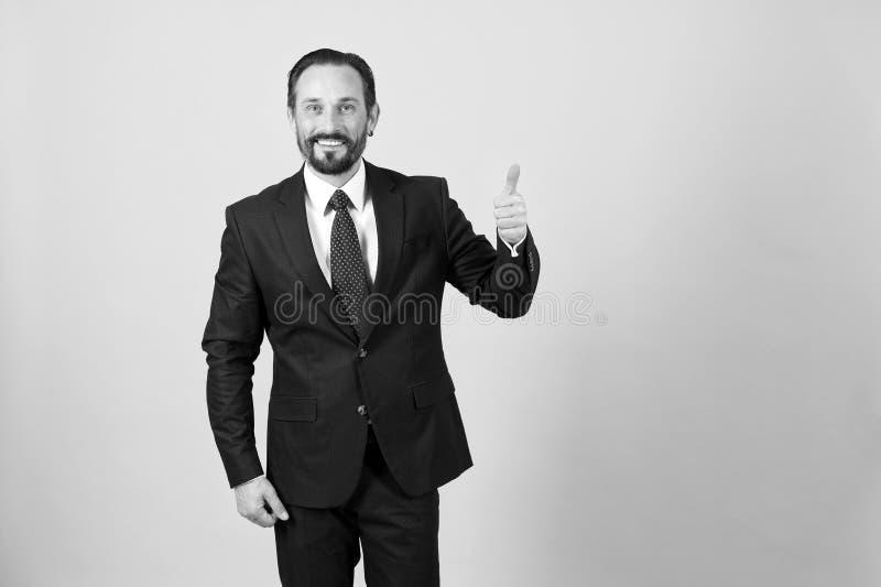 Hombre de negocios en pulgar oscuro del traje para arriba en el fondo blanco aislado adentro imagen de archivo libre de regalías