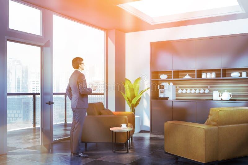 Hombre de negocios en salón de la oficina con la máquina del café foto de archivo